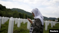 Hajra Catic prays near the grave of her husband in Potocari on June 23. She is still looking for her son, Nihad, who was 26 when Srebrenica fell.