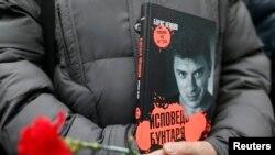 Человек с книгой Бориса Немцова и гвоздиками в руках.