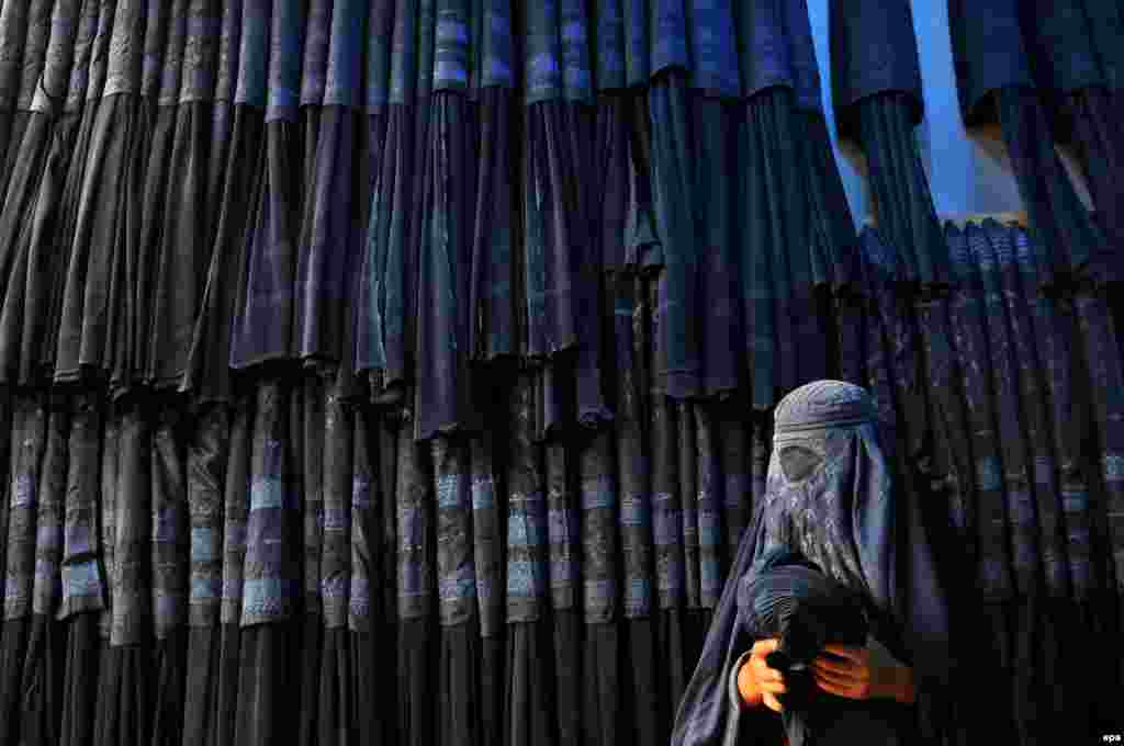 An Afghan woman buys a traditional burqa at a shop in Mazar-e Sharif. (epa/Sayed Mustafa)