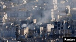 Smoke rises over an eastern Kobani neighborhood damaged by fighting between Islamic State militants and Kurdish forces on November 18.