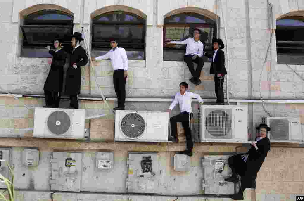 Israeli ultra-Orthodox Jews watch as police work at the scene after a Palestinian man rammed an excavator into a bus in Jerusalem on August 4, killing one person and slightly injuring five others. (AFP/Gali Tibbon)