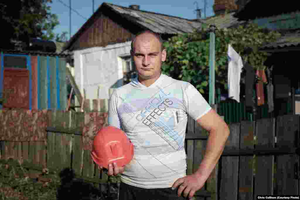 Sergei Dorokh stands with his mining helmet outside his home in the economically depressed neighborhood of Starayakolona in Myrnohrad. Dorokh worked in mining for five years before getting a job as a rescue worker at a local emergency service, responding to accidents at mining facilities in the region. The World Bank and other critics say Ukrainian mines have obsolete equipment and dangerous working environments.