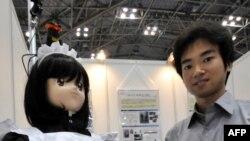 Сайтама университетинин профессору Юшинори Кобаяши роботторго арналган көргөзмөдө робот менен конокторго шоколад таратып жүрөт. Токио. 29-июль, 2010