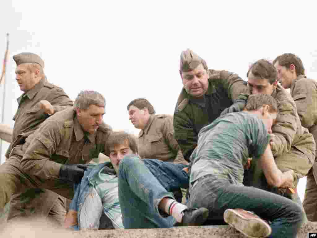 Көнчыгыш Германия хәрбиләре 1989 елның 11 ноябрендә Потсдам мәйданы янында кешеләрне Берлин диварыннан бәреп төшерергә маташа.
