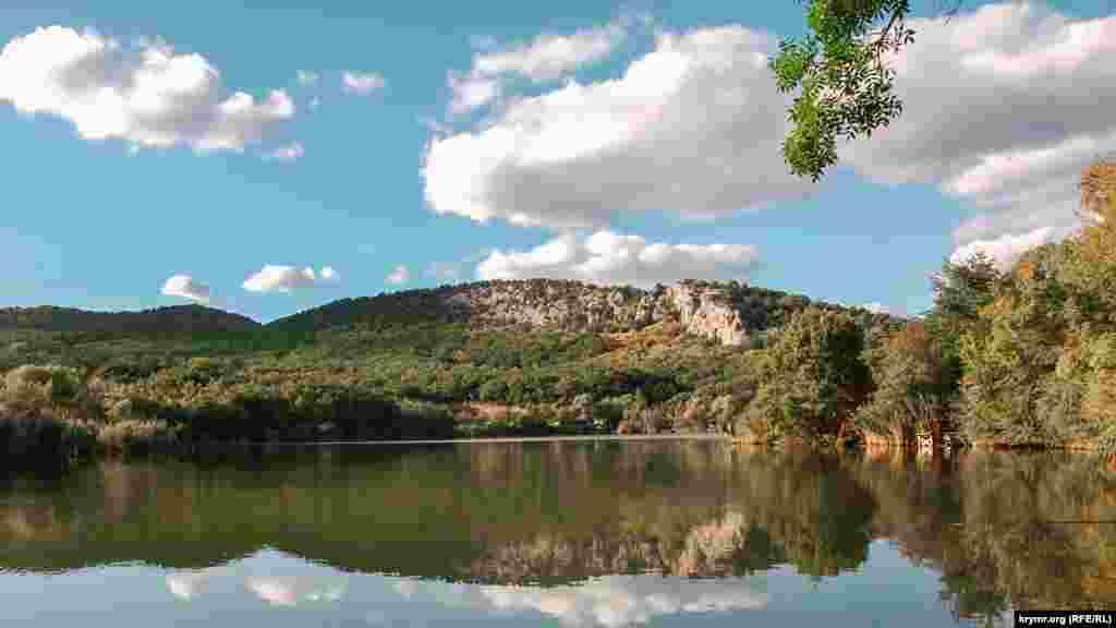 В солнечную погоду в спокойной воде озера отражаются облака