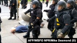 75-летний Мартин Гуджино (в синем) после удара полицейского