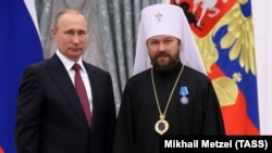 Russian President Vladimir Putin (left) awards Metropolitan Ilarion of Volokolamsk with an Order of Honor during a ceremony at the Moscow Kremlin in September 2016.