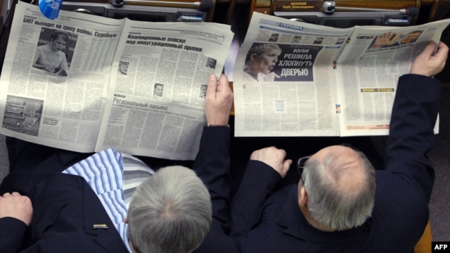 Ukrainian parliament deputies catching up on the news.