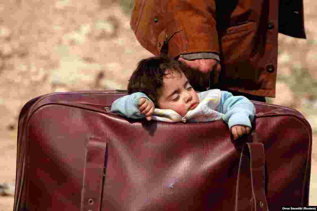 A child sleeps in a suitcase in the village of Beit Sawa, eastern Ghouta, Syria. A war monitor said that almost 20,000 civilians fled the Syrian town of Hammuriyeh and its surrounding areas in the rebel enclave of Eastern Ghouta. (Reuters/Omar Sanadiki)