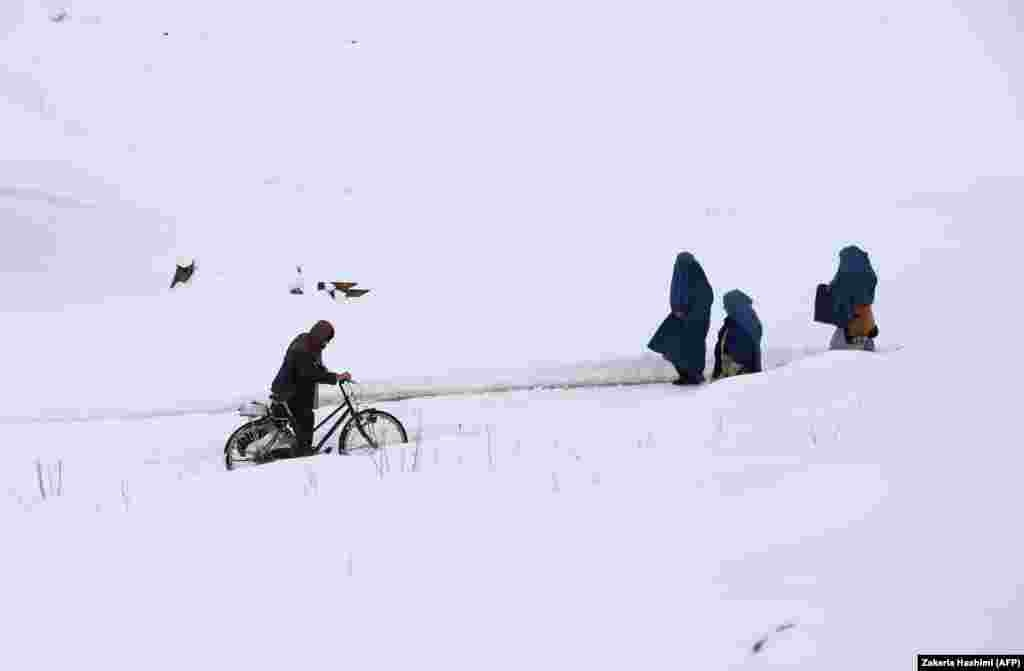 Afghan residents walk through a section of the old city amid snowfall in Ghazni. (AFP/Zakeria Hashimi)