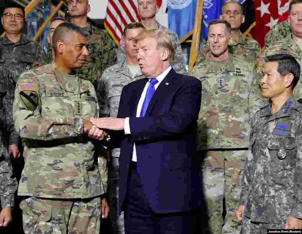 ЈУЖНА КОРЕЈА - Американскиот претседател Доналд Трамп со американските војници во базата на САД во Јужна Кореја. Трамп бил принуден да ја прекине својата ненадејна посета на демилитаризираната зона која ги дели двете Кореи. Според официјалните информации, хеликоптерот со кој се превезувал американскиот претседател бил вратен од пат кон зоната поради густа магла.