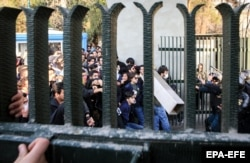 Iranian students clash with riot police during an antigovernment protest around the University of Tehran on December 30.
