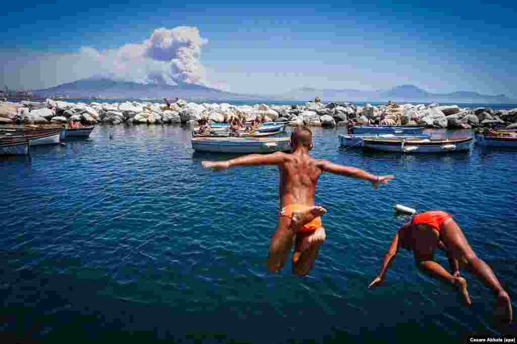 Children jump into the sea as smoke billows from fires around the Mount Vesuvius volcano in Naples, Italy, on July 11. (epa/Cesare Abbate)