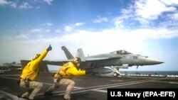 Lt. Nicholas Miller, from Spring, Texas, and Lt. Sean Ryan, from Gautier, Mississippi, launch an F/A-18E Super Hornet from the 'Pukin' Dogs' of Strike Fighter Squadron (VFA) 143 on the flight deck of the Nimitz-class aircraft carrier USS Abraham Lincoln. File phorto