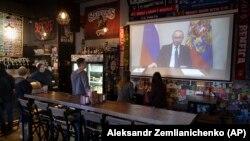 Посетители и работники паба в Москве смотрят обращение Владимира Путина к россиянам, 25 марта 2020 года