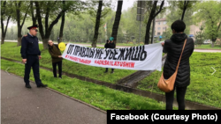 Асия Тулесова и Бейбарыс Толымбеков с баннером. Алматы, 21 апреля 2019 года.