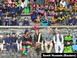 The royal pair wait for dancing to begin at a settlement of the Kalash people in the Chitral District.