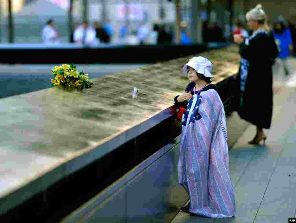 Ava Kathleen Schmoelzer, age 7, places flowers by the memorial pool at the World Trade Center site in memory of her aunt during commemorations on the eleventh anniversary of the attacks.