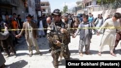 Сотрудник сил безопасности Афганистана у места атаки смертника в Кабуле. 22 апреля 2018 года.