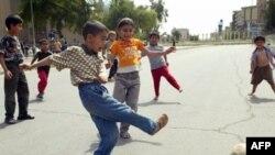 اطفال عراقيون يلعبون الكرة في احد شوارع بغداد