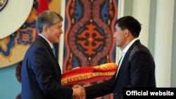 Президент Алмазбек Атамбаев вручает государственный флаг капитану олимпийской сборной Кыргызстана Данияру Кобонову, Бишкек, 16 июля 2012 года.