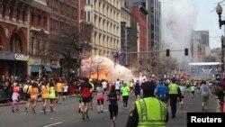 متسابقون يواصلون الركض مع حدوث إنفجار قرب خط النهاية لماراثون بوسطن.