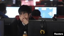 Молодой китаец сидит за компьютером в интернет-кафе. Иллюстративное фото.