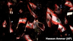 Demonstranti mašu libanskim zastavama uzvikujući parole protiv libanske vlade tokom protesta u Bejrutu, 21. oktobra 2019.