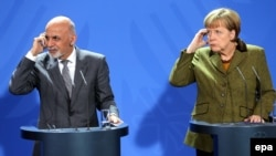 German Chancellor Angela Merkel (R) and Afghan President Ashraf Ghani take part in a press conference at the Federal Chancellery in Berlin on December 5.