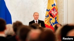 Russian President Vladimir Putin on March 18, 2014, addresses the Federal Assembly, including State Duma deputies, members of the Federation Council, regional governors, and civil society representatives on the annexation of Ukraine's Crimea region.