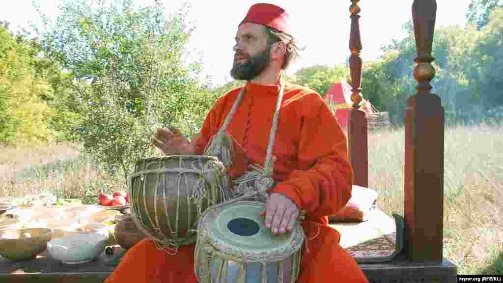 Торговець грає на барабанах, заманюючи покупців у свою польову крамницю