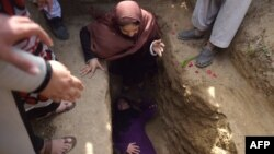 FILE: Afghan civil society activist women weep and lie on the grave of Afghan woman Farkhunda, 27, who was lynched by an angry mob, at the cemetery in central Kabul in March 2015.