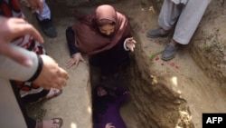 Afghan civil society activist women weep and lie on the grave of Afghan woman Farkhunda, 27, who was lynched by an angry mob in central Kabul in March.