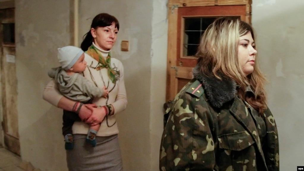 Женщина-заключенная с ребенком направляется на тюремное богослужение. Донецк, 17 декабря 2014 года