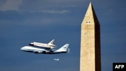 "The space shuttle ""Discovery,"" sitting atop NASA's 747 shuttle carrier aircraft, flies over the Washington Monument."