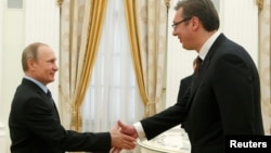 Russian President Vladimir Putin (left) greets Serbian Prime Minister Aleksandar Vucic during the latter's visit to Moscow in May, not long after Serbia's parliamentary elections.