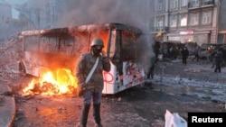Protestçi otlanan polisiýa awtobusynyň öňünde dur. Kiýew, 20-nji ýanwar, 2014.