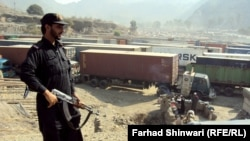 A Pakistani security officer stands guard over long lines of NATO trucks and oil tankers at a border crossing amid a blockade against NATO vehicles transporting supplies to Afghanistan via Pakistan. The blockade has been in place since November 26, when 2