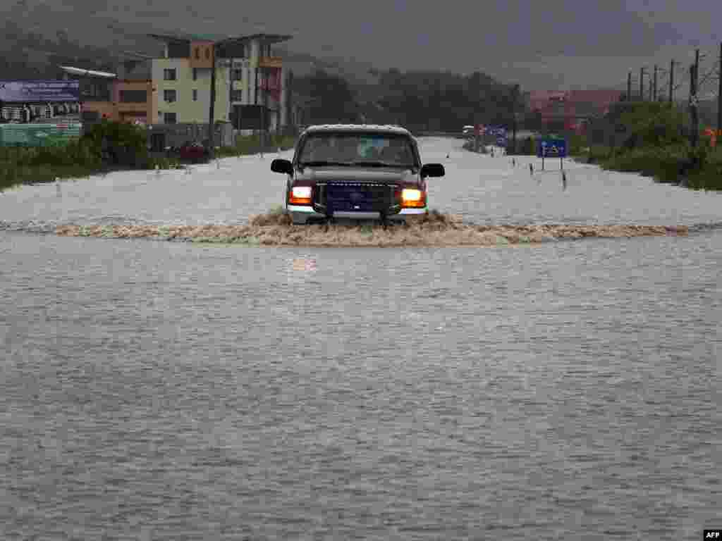 A car travels on a flooded road near the village of Jucu in Cluj, in the central Transylvania region of Romania, on June 23. (Photo by Mircea Rosca/AFP)