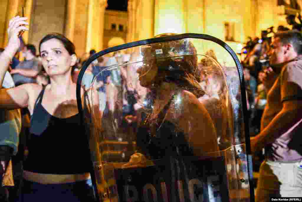 Protesters with police shields.