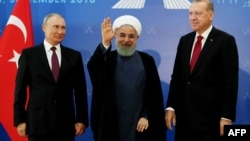 Turkish President Recep Tayyip Erdogan (right), Iranian President Hassan Rohani (center), and Russian President Vladimir Putin greet the media during a trilateral summit in Tehran on September 7.