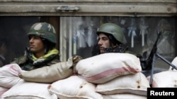 Syrian soldiers man a checkpoint in Homs on January 23.