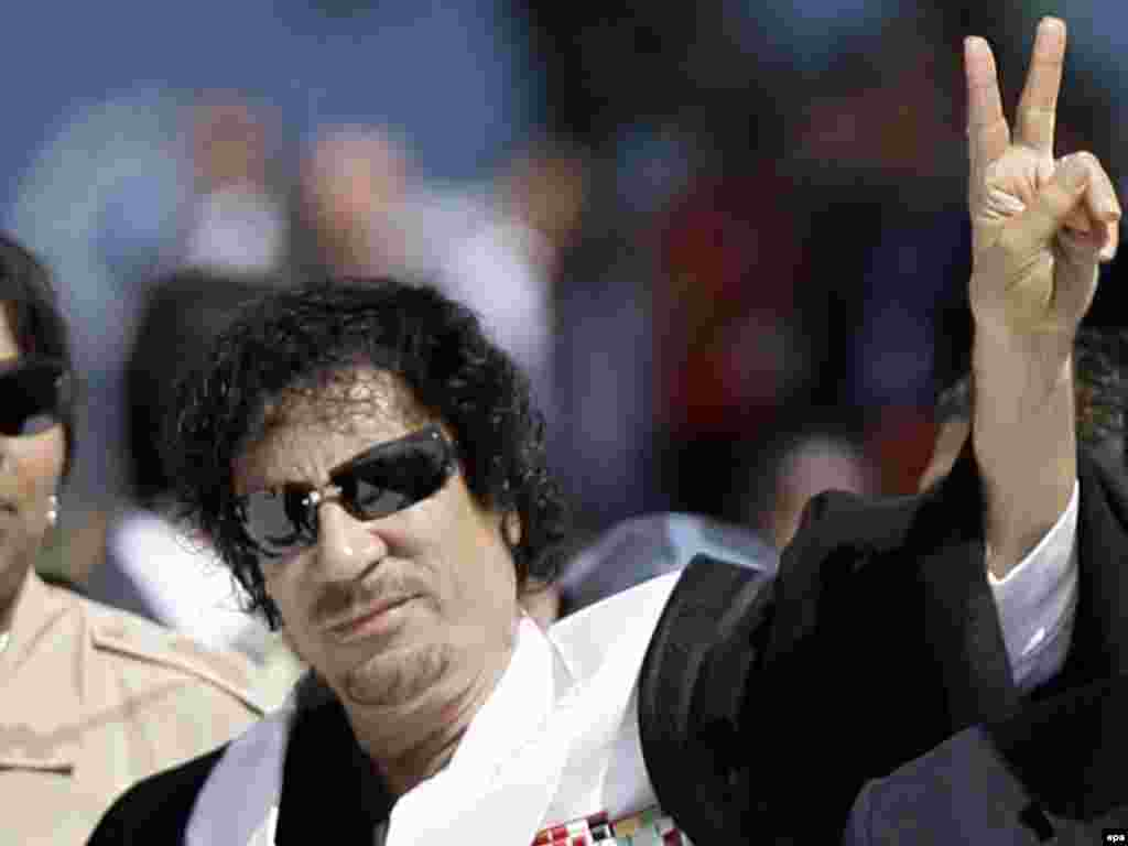 Qaddafi makes the victory sign as he arrives for a session at the G8 summit in L'Aquila, Italy, on July 10, 2009.