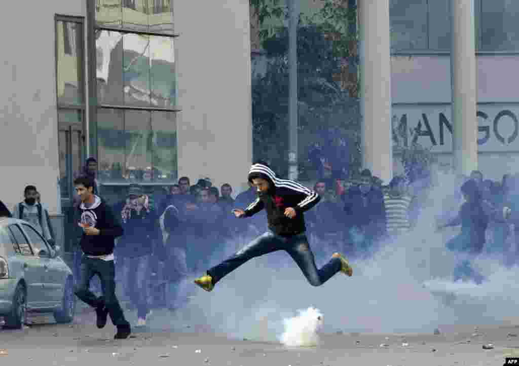 A Tunisian protester jumps amid smoke after police fired tear gas during a rally outside the Interior Ministry in Tunis to protest after opposition leader and outspoken government critic Chokri Belaid was shot dead. (AFP/Fethi Belaid)