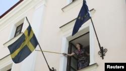 Супрацоўніца швэдзкай амбасады ў Менску папраўляе сьцяг, 8 жніўня 2012