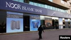A woman walks past a branch of Noor Islamic Bank in Dubai.
