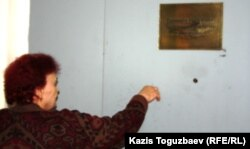 Женщина стучится в ворота центра психиатрии, чтобы передать еду для своего родственника, пациента этой клиники. Алматы, 8 мая 2013 года.