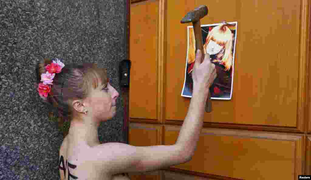 An activist from the women's rights group Femen nails a photo of her sister to a door as she protests against her kidnapping outside the Ukrainian Security Service (SBU) headquarters in Kyiv. (Reuters/Valentyn Ogirenko)