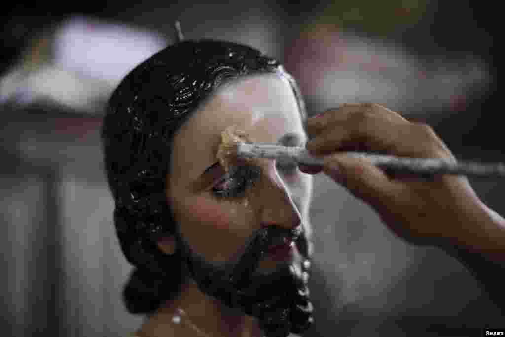 Хозе Гомес наносит тальк на лицо статуи Иисуса Христа в своей мастерской вАпастепеку. Тальк нужен, чтобы заполнить поры дерева и чтобы краска лучше держалась на поверхности скульптуры