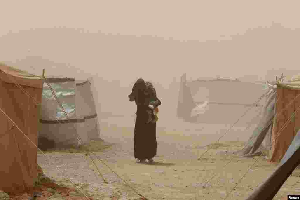 Një grua që iku nga Falluxha për shkak të dhunës së Shtetit Islamik, mban fëmijën e saj gjatë një stuhie pluhuri në një kamp refugjatësh në Amiriyat Falluxha, në Irak.